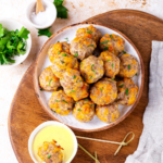 An overhead view of several keto sausage balls on a white plate. The plate is on a wooden cutting board and there is dipping sauce in front of the plate at the edge of the cutting board. A keto sausage ball is in the dipping sauce and there is a toothpick in it.
