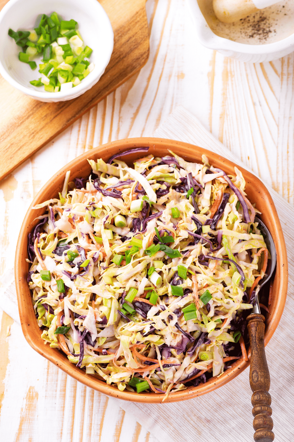 An overhead view of keto coleslaw in a wooden bowl. A spoon is emerged in the keto coleslaw and the bowl is on a white tablecloth on a wooden counter.