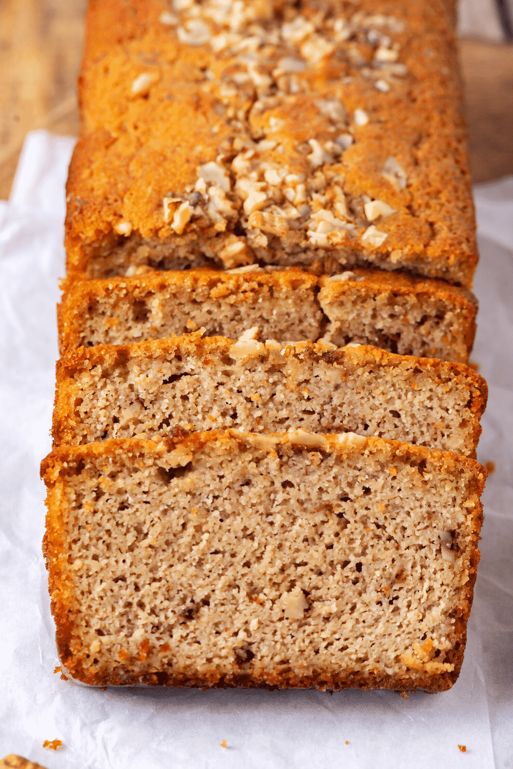 A banana bread loaf with three slices cut leaning up against the front of the loaf. The banana bread is on a piece of white parchment paper.
