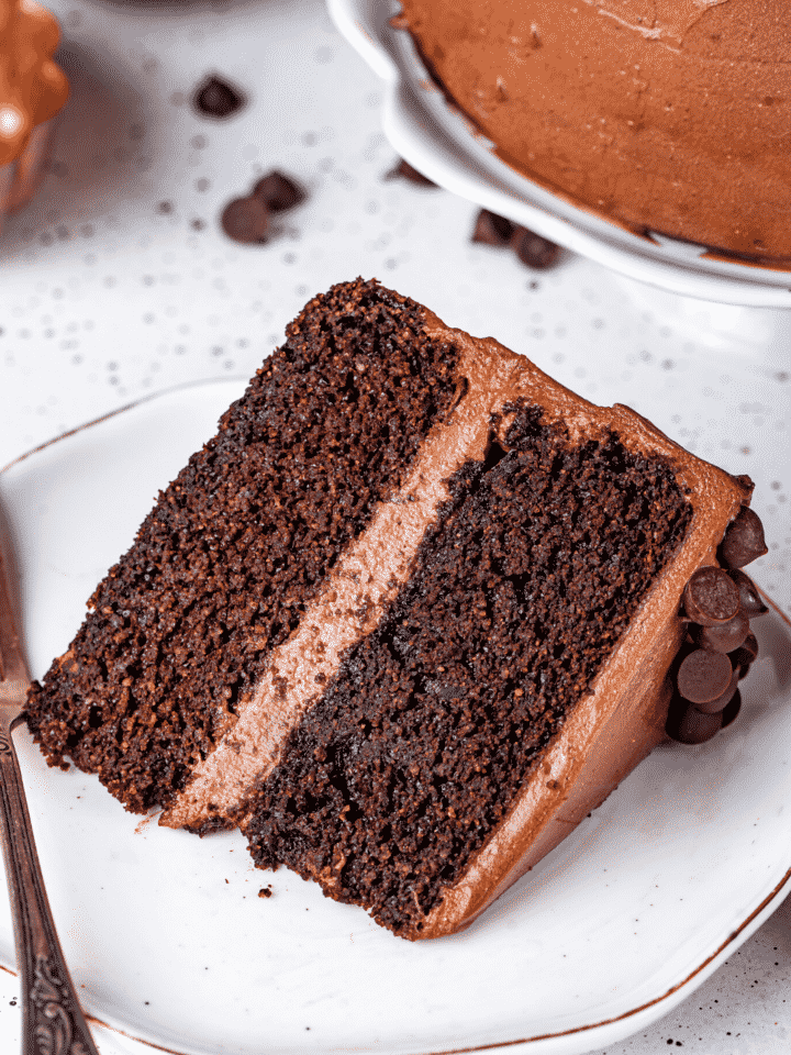 A slice of chocolate cake lying on its side on a white plate.