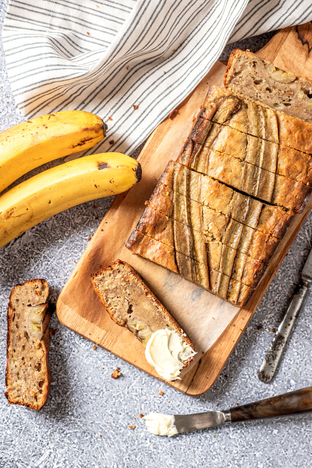 A loaf of vegan banana bread sliced into pieces. A piece is cut out of the front of the loaf laying down with a slab of butter on it. Another piece is in front of the cutting board laying face down.