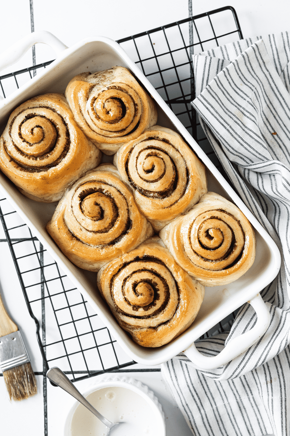 A square baking dish filled with six cinnamon rolls. The baking dish is on a black wire rack.