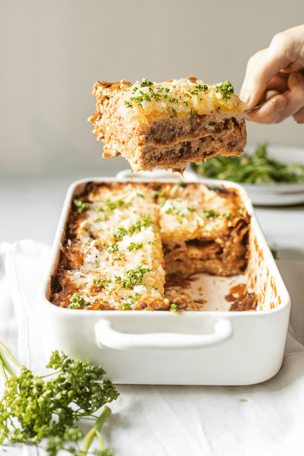 A baking dish filled with vegan lasagna. A few sliced of lasagna are taken out of the dish and a hand is holding a server above the dish with a piece of vegan lasagna on it.