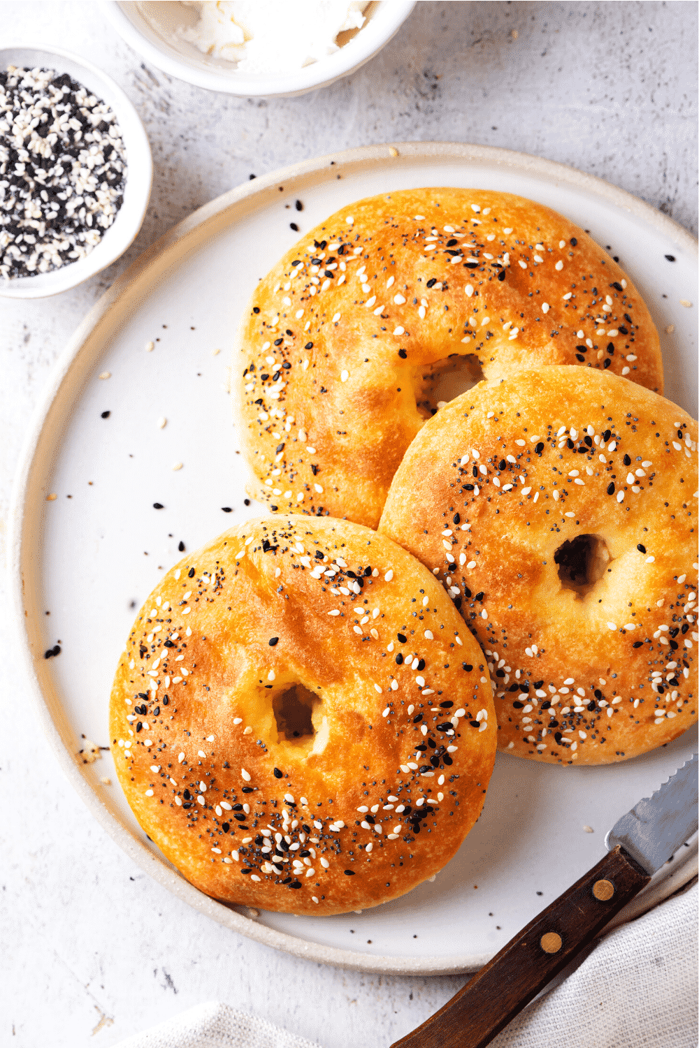 Three bagels overlapping one another on a white plate. There are small bowls of seasoning and butter behind