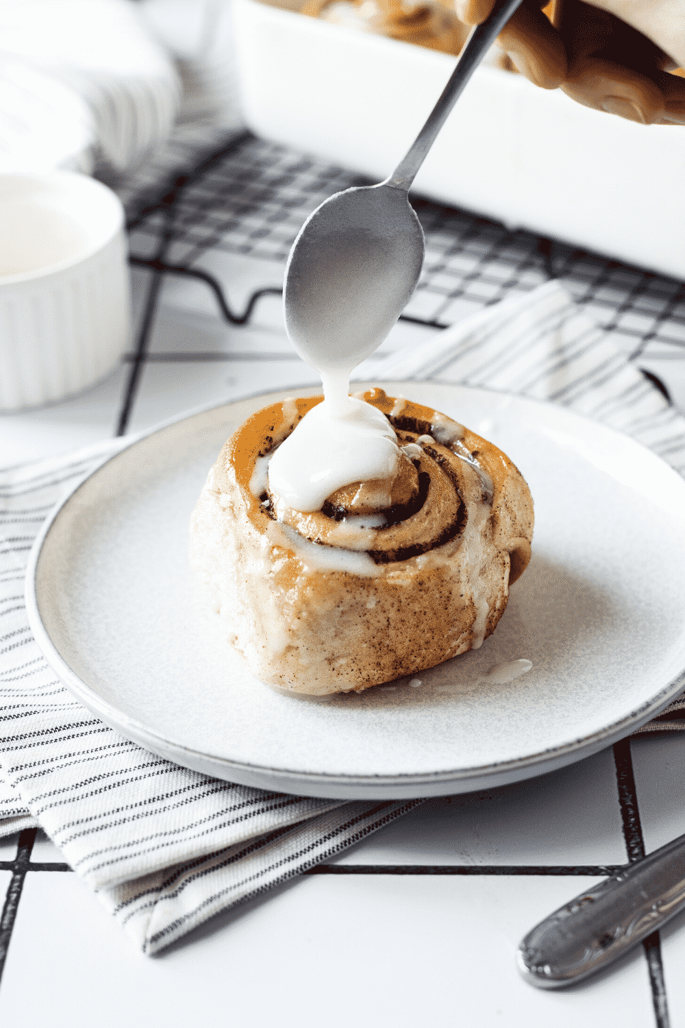 A white plate with a cinnamon roll on it. A spoon is hovering over the cinnamon roll drizzling icing on top.