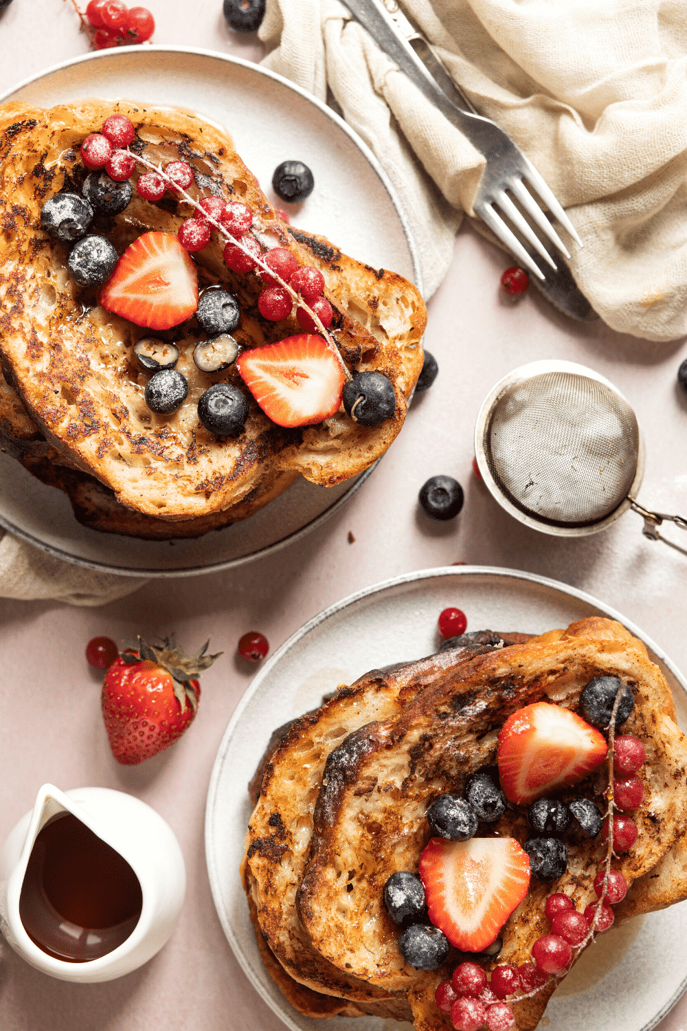 Two white plates with a few pieces of French toast stacked on top of one another on them. There is fresh fruit on the top slice of each piece and there is some fruit surrounding the white plates.