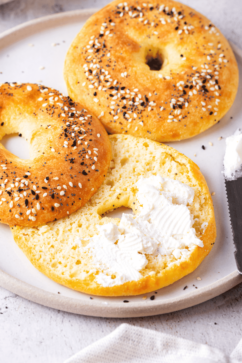 Two bagels on a white plate. A whole bagel is at the back of the plate and a sliced bagel is at the front. The sliced bagel has butter spread on the bottom half of it.