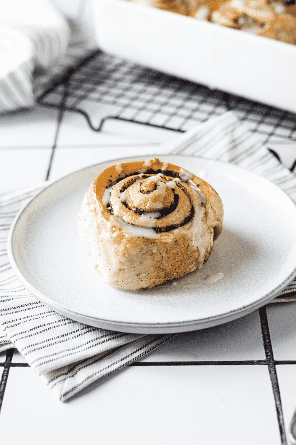 A white plate with a cinnamon roll on it. The plate is on a white stripped napkin on a white counter.