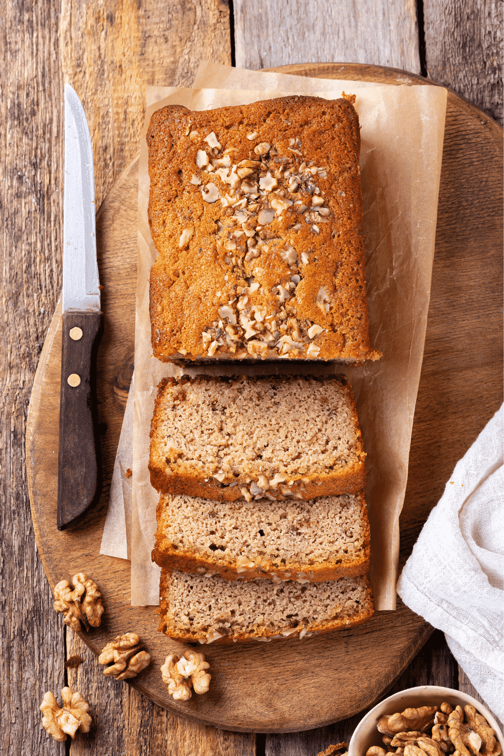 A loaf of banana bread and a piece of white parchment paper on a wooden cutting board. Three pieces of the banana bread are sliced and are in front of the loaf overlapping one another. A knife is to the left of the banana bread and there are a few walnuts in front of it