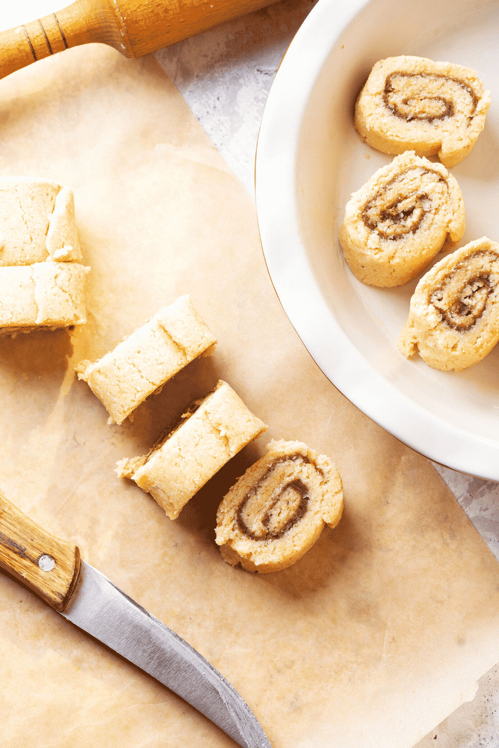 A roll of cinnamon rolls cut into five individual cinnamon rolls on a piece of parchment paper. Three other cut cinnamon rolls are in a white baking dish to the right of the piece of parchment paper.