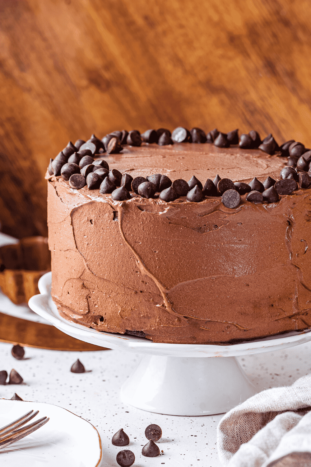A whole chocolate cake on a white serving dish.