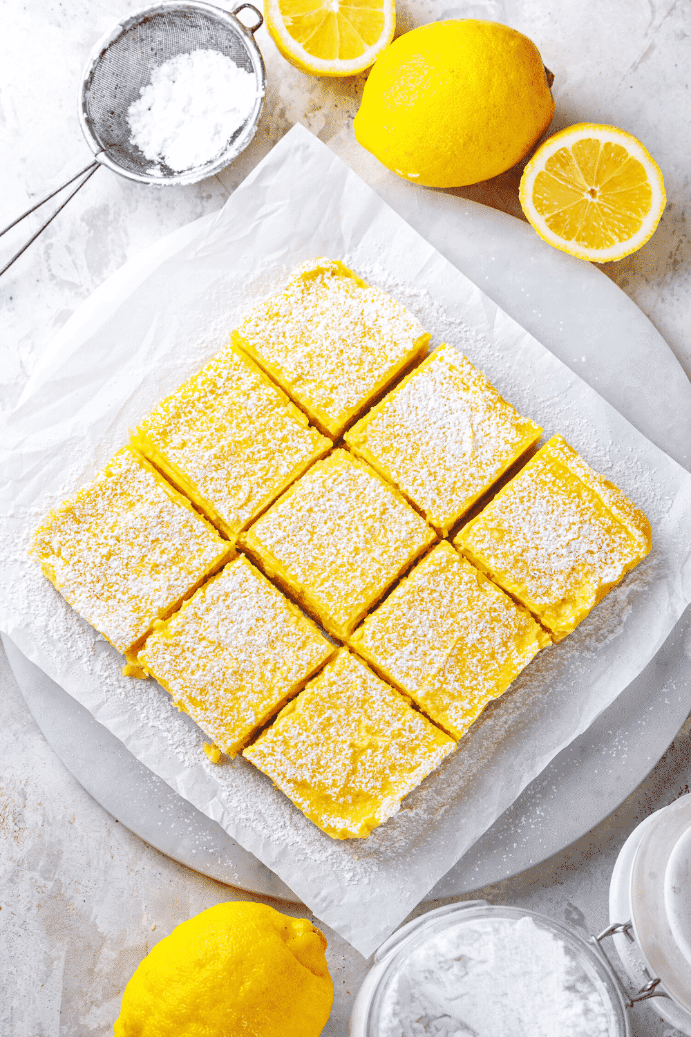 And overhead view of three rows of three lemon bar squares. The lemon bars are on a piece of white parchment paper and they are covered in powdered sugar.