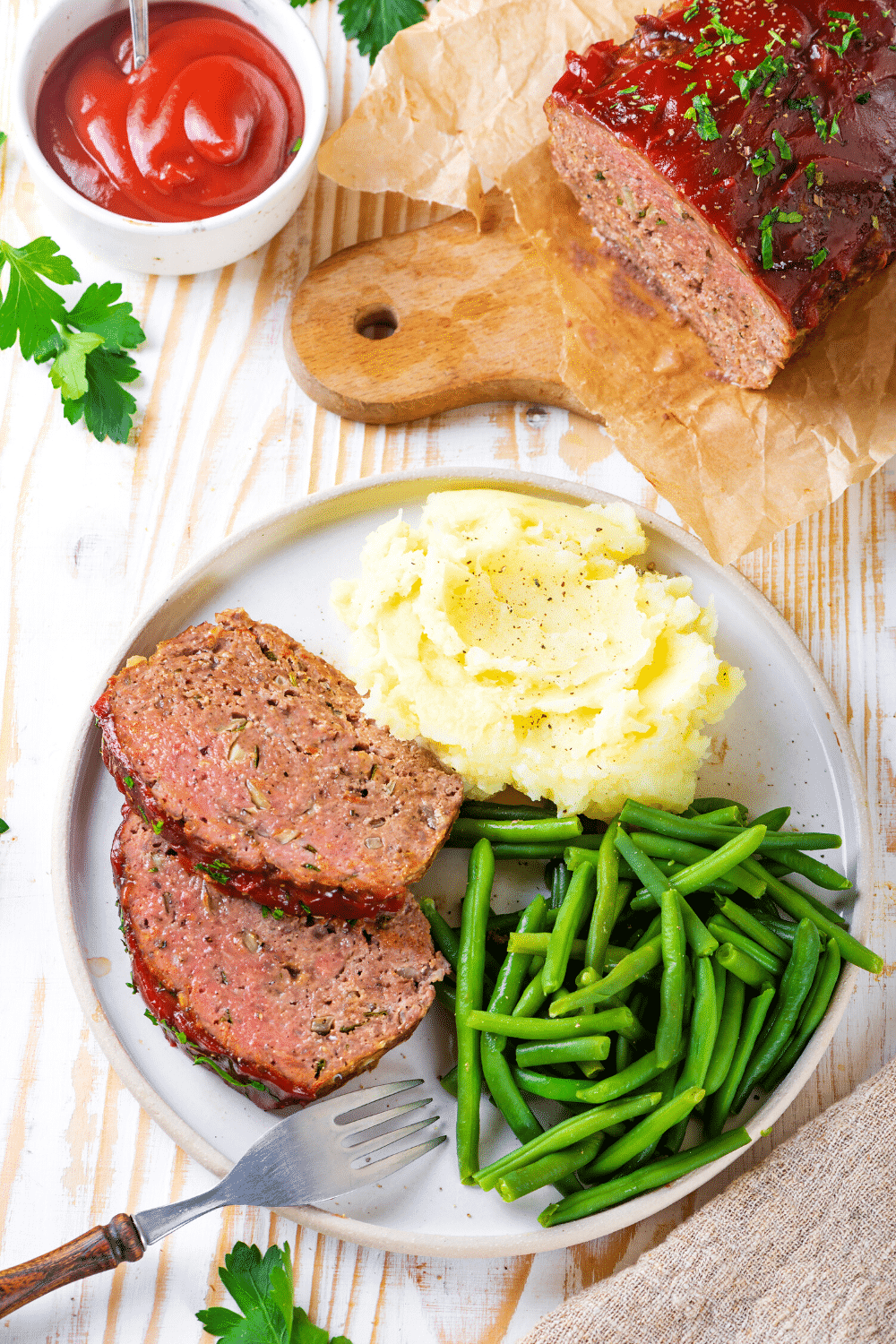 A white plate with two slices of meatloaf mashed potatoes and green beans. The whole meatloaf is behind the plate on a piece of white parchment paper on a wooden cutting board.