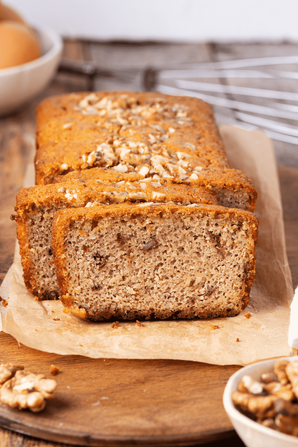 A loaf of banana bread on a piece of parchment paper on a wooden cutting board. The front of the loaf is cut into slices.