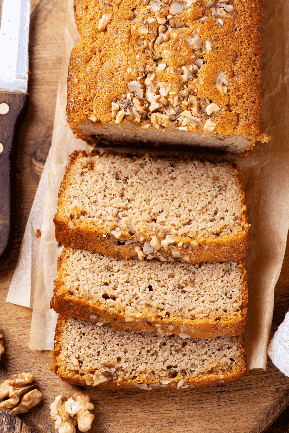 An overhead view of a banana bread loaf. Three pieces of banana bread are sliced and are lying in front of the loaf overlapping one another.