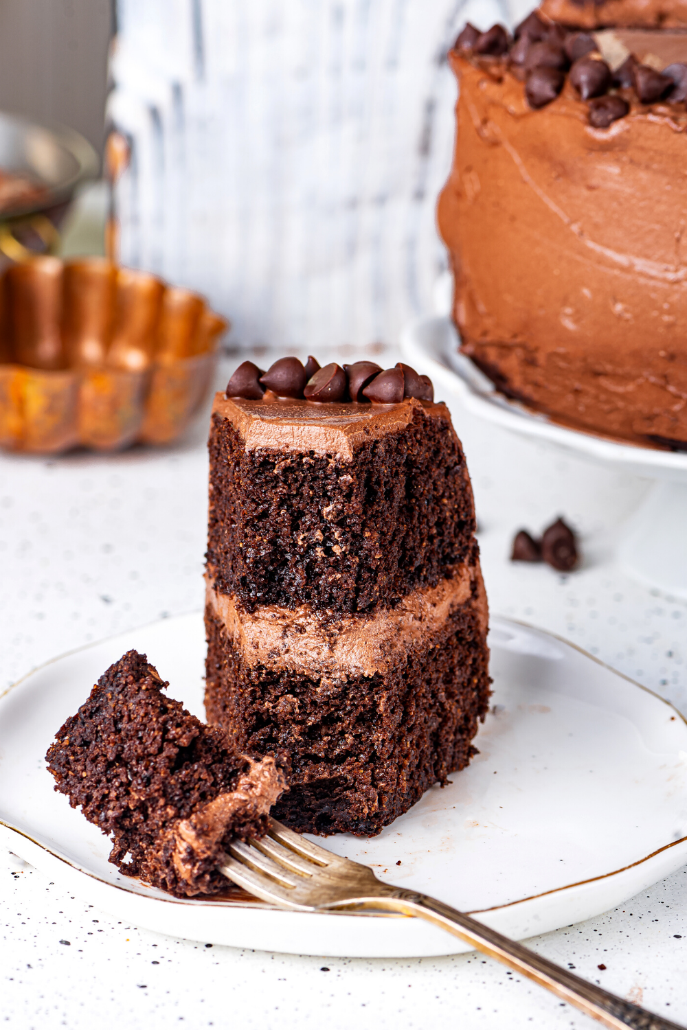 A slice of chocolate cake on a white plate with a fork in front of the cake. There is some of the chocolate cake on the prong of the fork.