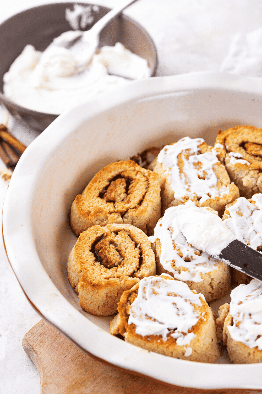 A white baking dish filled with two cinnamon rolls, three cinnamon rolls with icing on them, and then three more cinnamon rolls to the right of those.