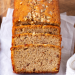 A loaf of banana bread and a piece of white parchment paper on a wooden cutting board. Three pieces of banana bread are sliced and are leaning up against the front of the loaf.