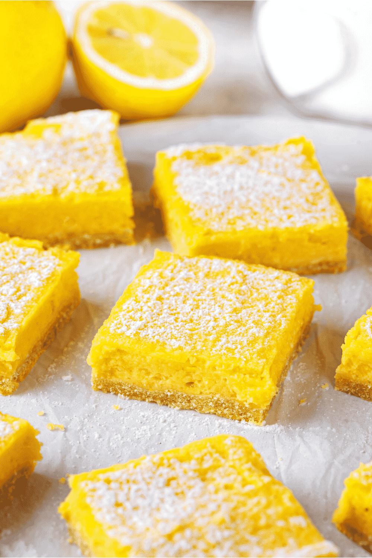 A few squares of lemon bars on a piece of white parchment paper.