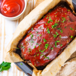 A meatloaf in a loaf pan with a piece of parchment paper underneath the meatloaf. A small cup of ketchup is to the back left of the meatloaf.