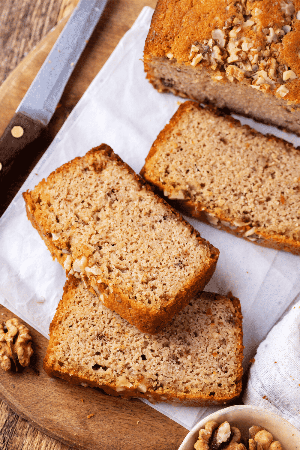 Three slices of banana bread on a piece of white parchment paper on a wooden cutting board.