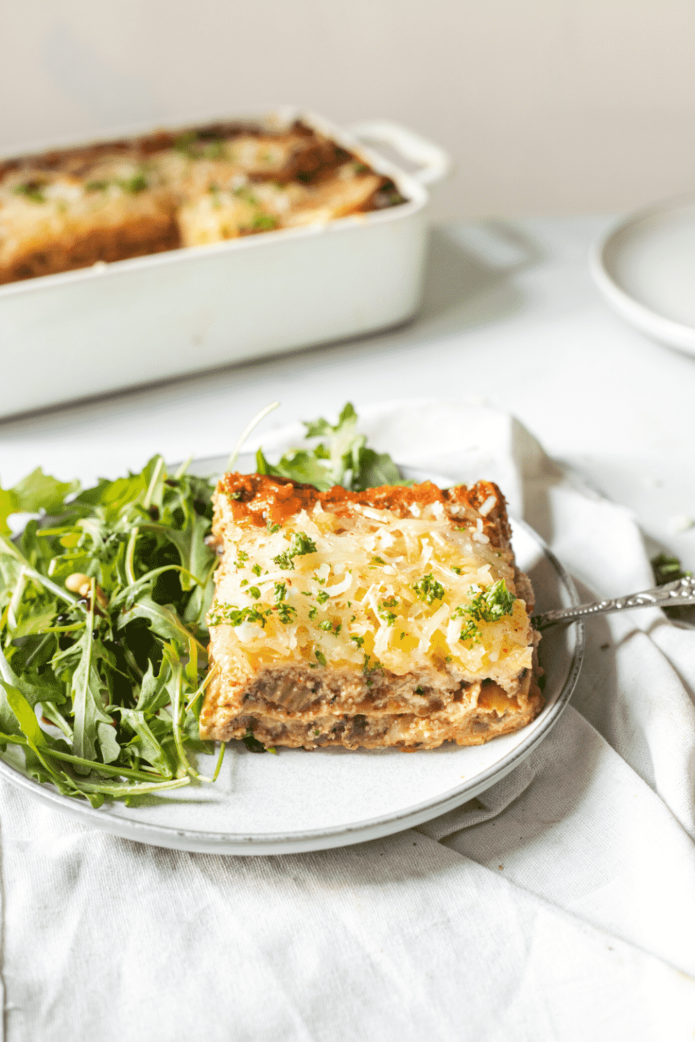 A white plate with vegan lasagna and arugula on it. There is a tray of lasagna behind the plate on a white counter.