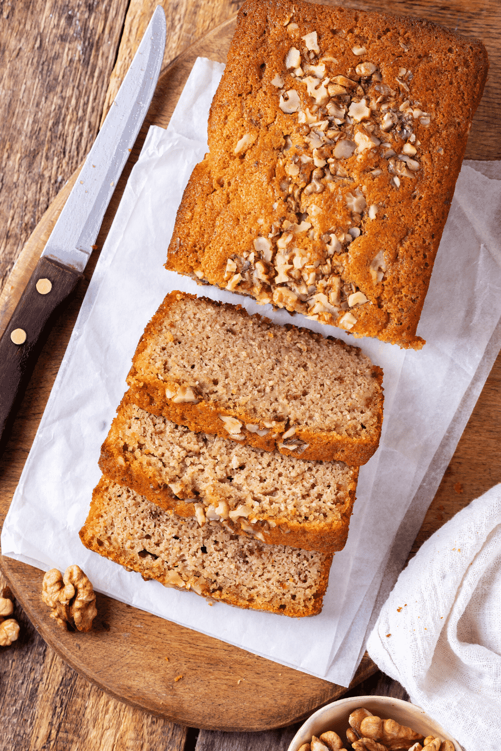 An overhead view of a banana bread loaf. Three pieces of banana bread are cut and are lying down.An overhead view of a banana bread loaf. Three pieces of banana bread are cut and overlapping one another in front of the loaf. A knife is next to the banana bread to the left.