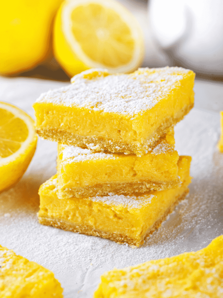 A stack of three keto lemon bars. The white counter the lemon bars are on is covered in powdered sugar.
