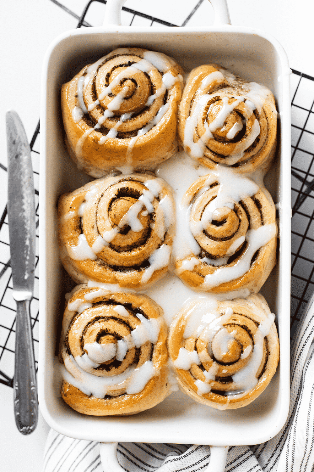 A white baking dish with six cinnamon rolls covered in icing. The baking dish is on a black wire rack on a white counter.