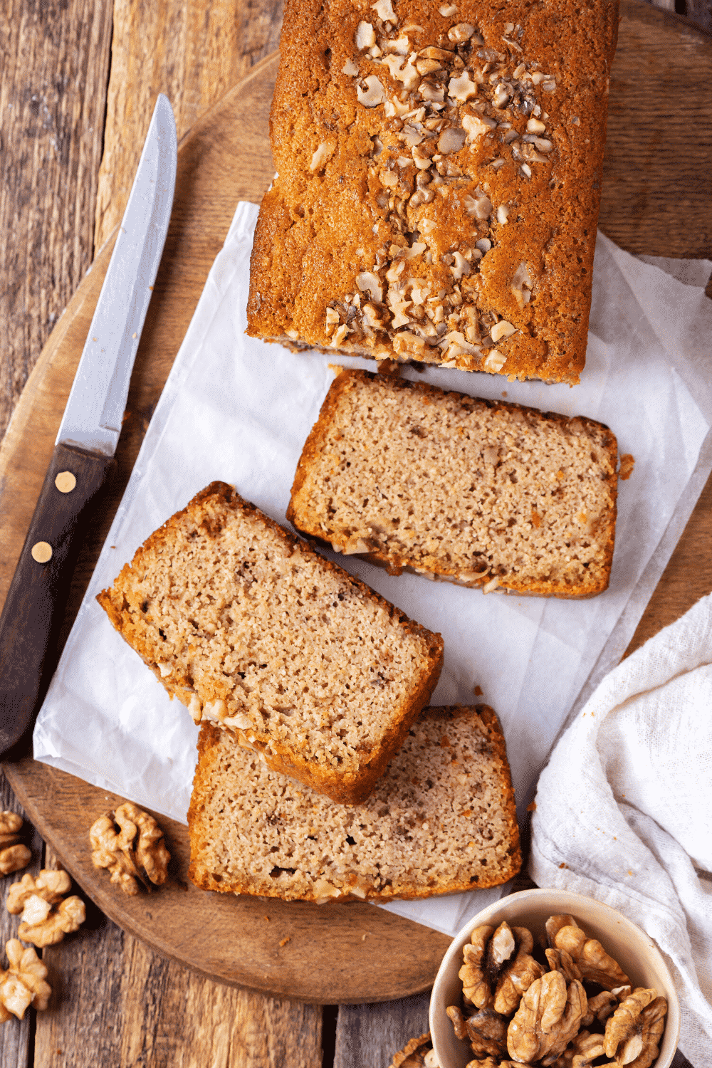 A banana bread loaf on a wooden cutting board with three cut pieces laying in front of the loaf. A knife is to the left of the banana bread and a small bowl of walnuts is in front of it.