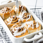 A square baking dish with six cinnamon rolls in it with a spoon hovering over the cinnamon rolls drizzle in icing on them.
