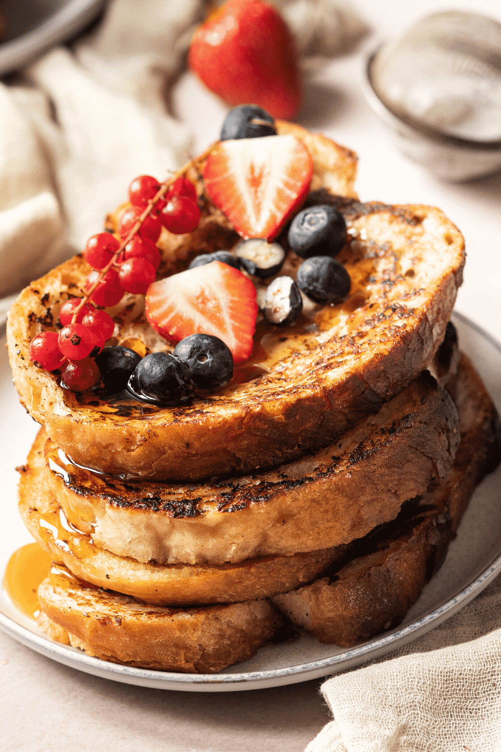 Four pieces of vegan French toast on a white plate with fresh fruit on the top slice of French toast.