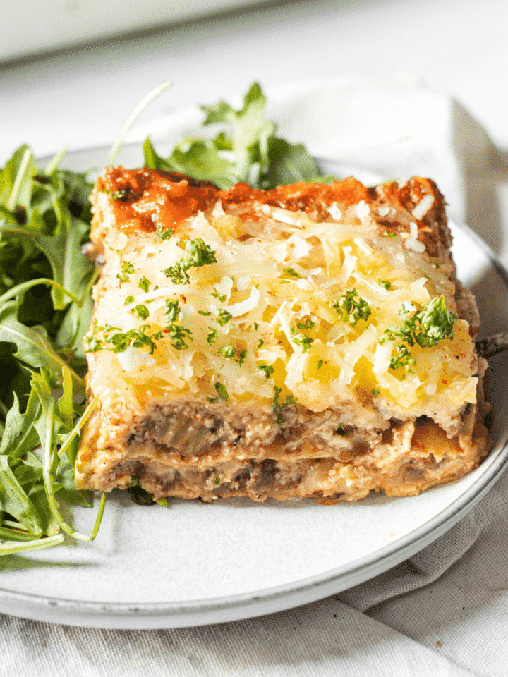 A white plate with a piece of vegan lasagna on it.