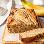 Loaf of banana bread on a piece of parchment paper on a wooden cutting board. There is a slice out of the loaf sitting in front of it and a bunch of bananas behind the loaf.