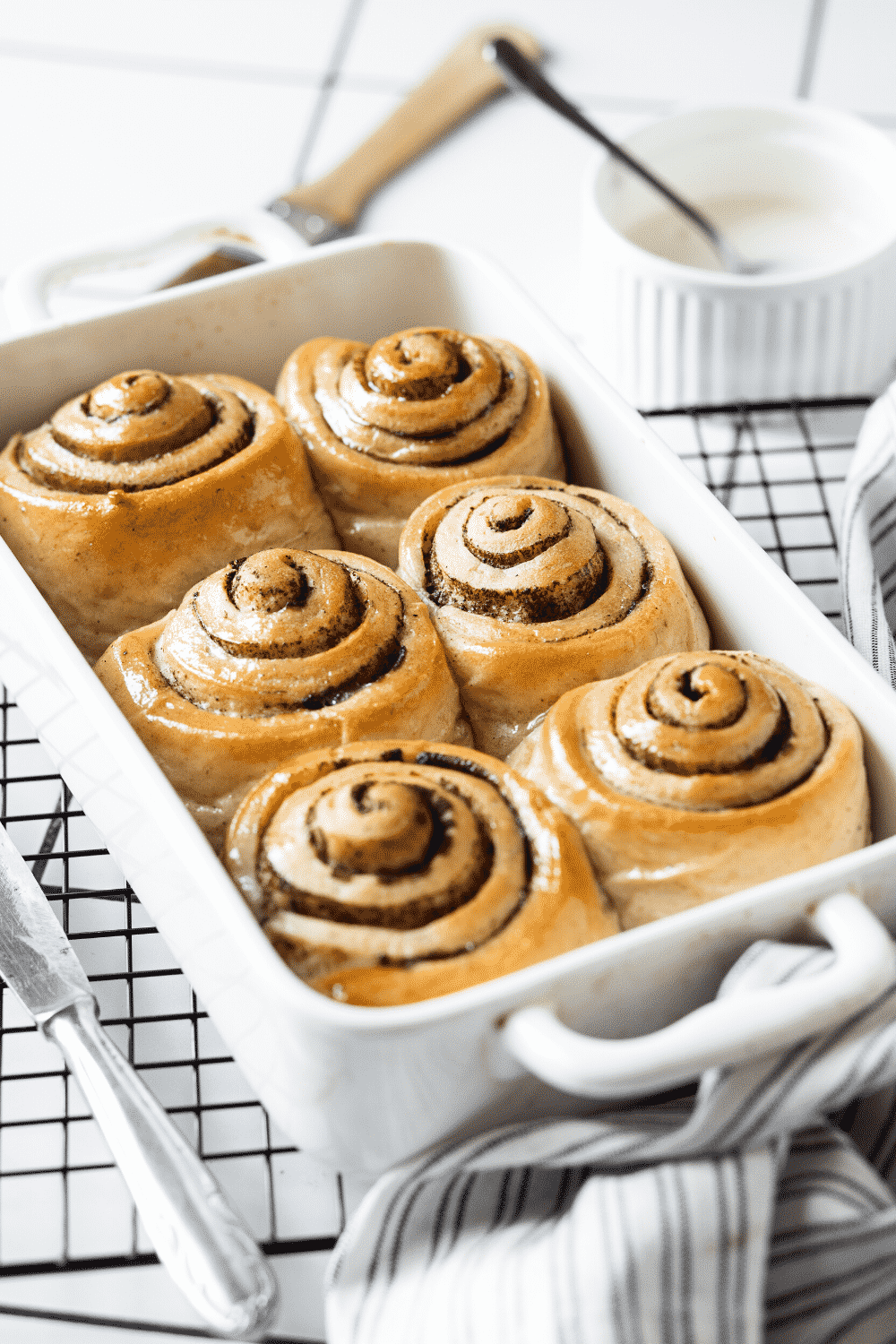 A white square baking dish with six cinnamon rolls in it. A cup of icing is behind the tray of cinnamon rolls.