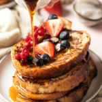Four slices of vegan French toast stacked on top of one another on a white plate. Fresh fruit is on the top slice of French toast and maple syrup is being poured over the stack.