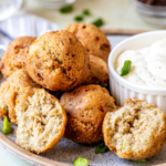 A blue speckled plate with a bunch of hush puppies on top of one another.