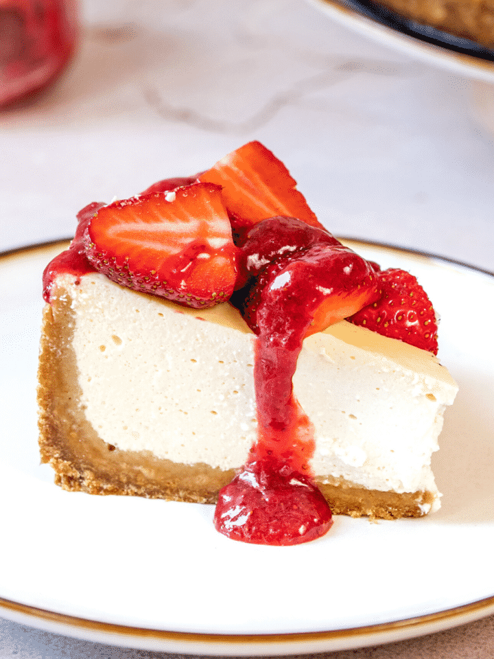A piece of strawberry cheesecake on a white plate.