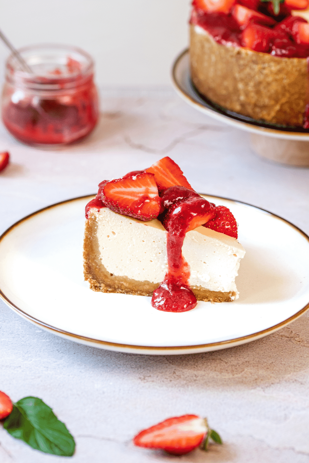 A piece of strawberry cheesecake on a white plate. There is a jar of the strawberry topping behind the plate on the white counter.