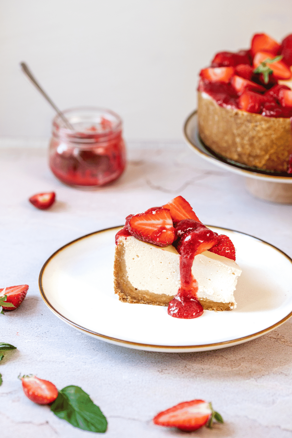 A piece of strawberry cheesecake on a white plate. Part of the strawberry cheesecake is showing behind the plate on the white counter..