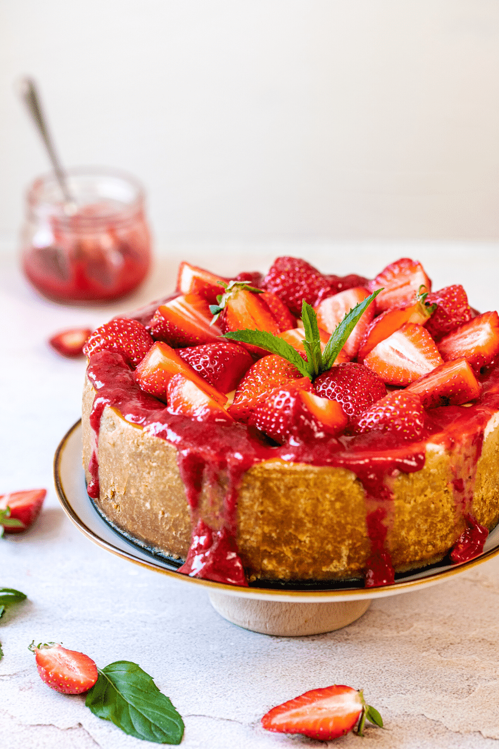 A strawberry cheesecake with sliced strawberries and strawberry sauce on top of it on a serving dish on a white counter.