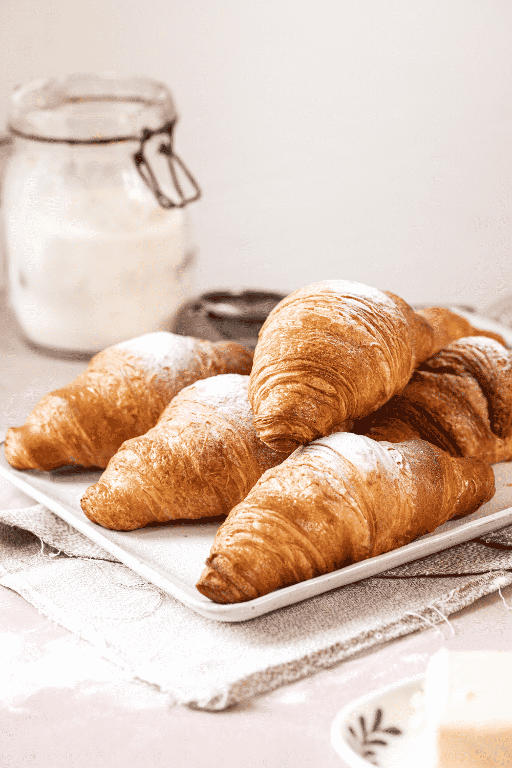 White rectangular plate with a bunch of croissants on it on top of one another. The white plate is on a white tablecloth on a pink counter.