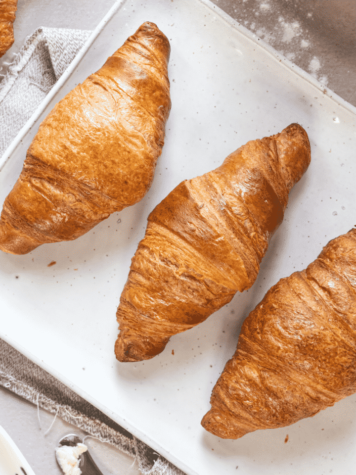 A white rectangular plate with three croissants on it.