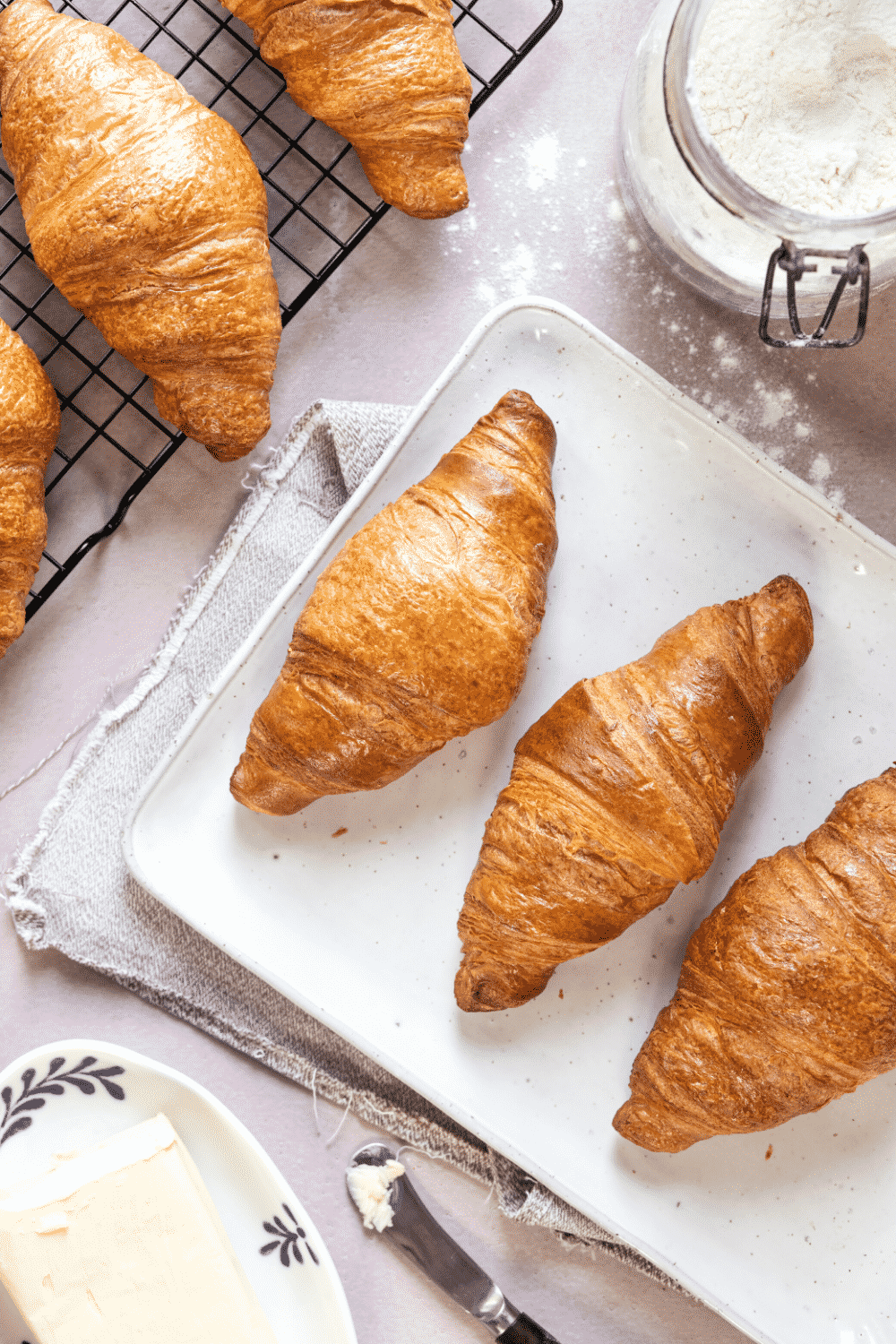 A white plate with three croissants on it. There is a black wire rack behind the plate with a croissant on it.