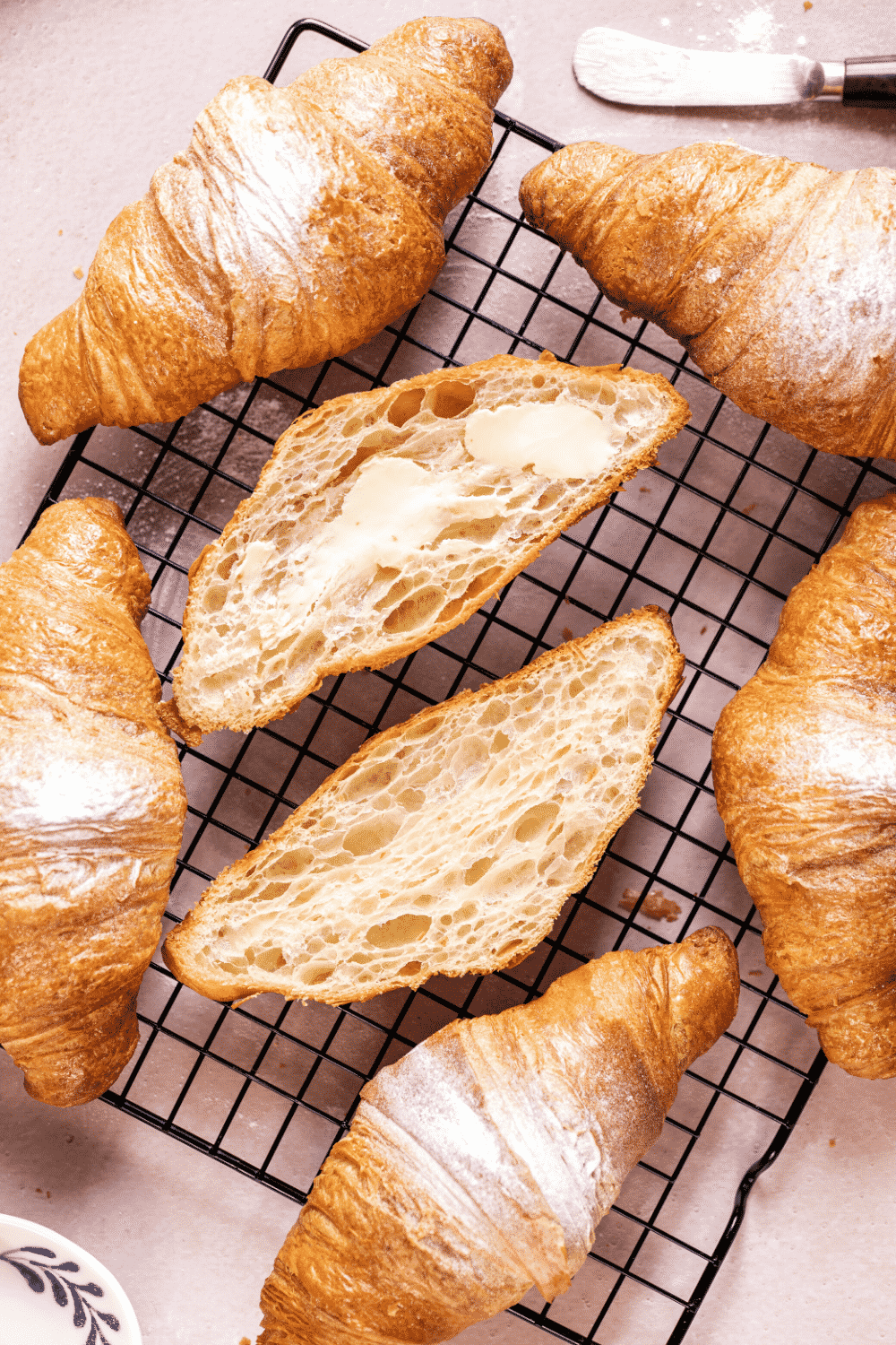 A black wire rack with six croissants on it. One croissant is broken in half with the inside facing up.