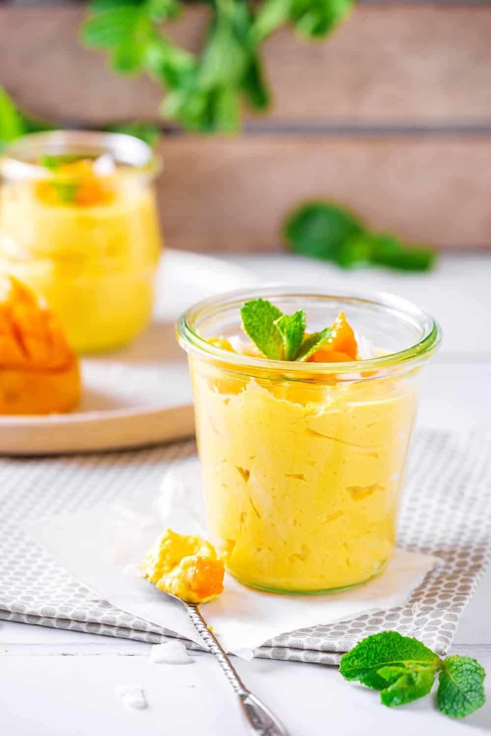 A glass cup filled with mango mousse on a napkin set on a tablecloth on the white table. Hey spoon with a scoop of mango mousse on it is on the napkin.