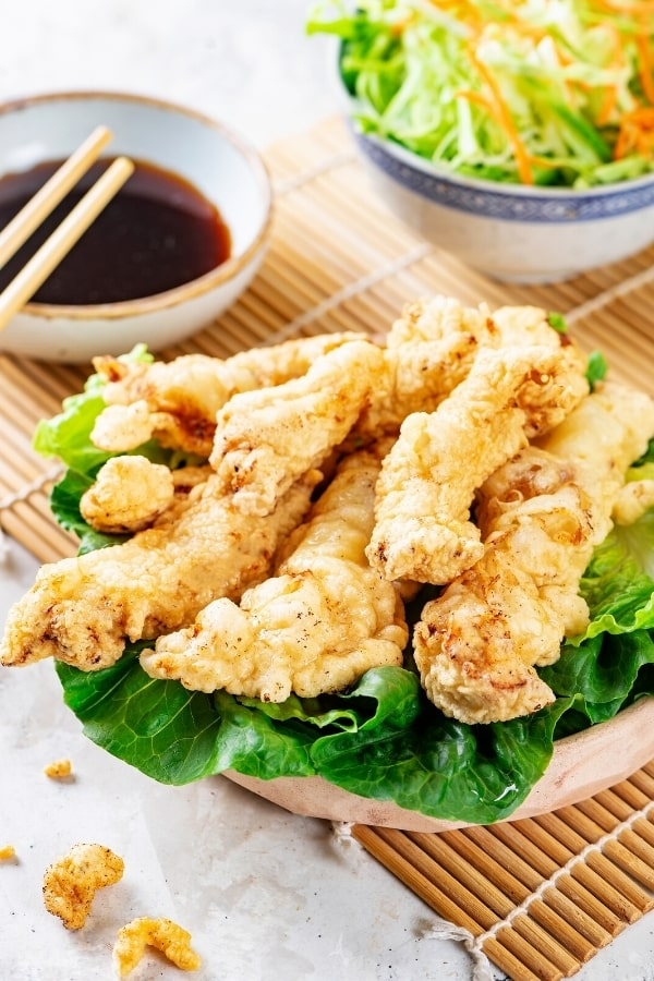 A wooden bowl filled with chicken tempura on top of lettuce leaves. Part of a small bowl of soy sauce and part of a small bowl of shredded cabbage is behind it.