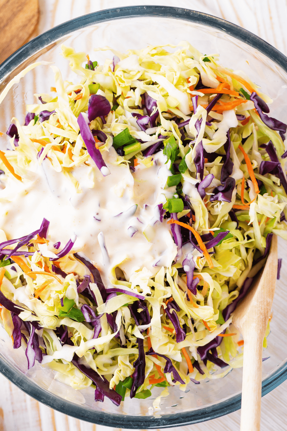 A glass bowl filled with coleslaw mix with coleslaw dressing on top.