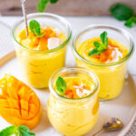 3 glass cups of mango mousse on a white plate. There is diced mango and coconut flakes on top of the mousse.
