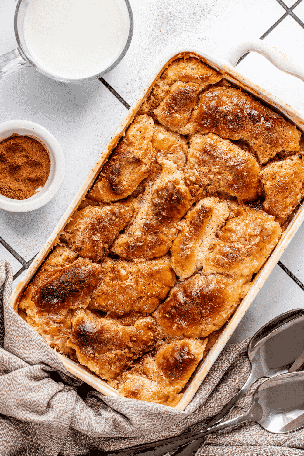 A white casserole dish with bread pudding in it. There is a small bowl of cinnamon and a small cup of milk to the left of the bowl.